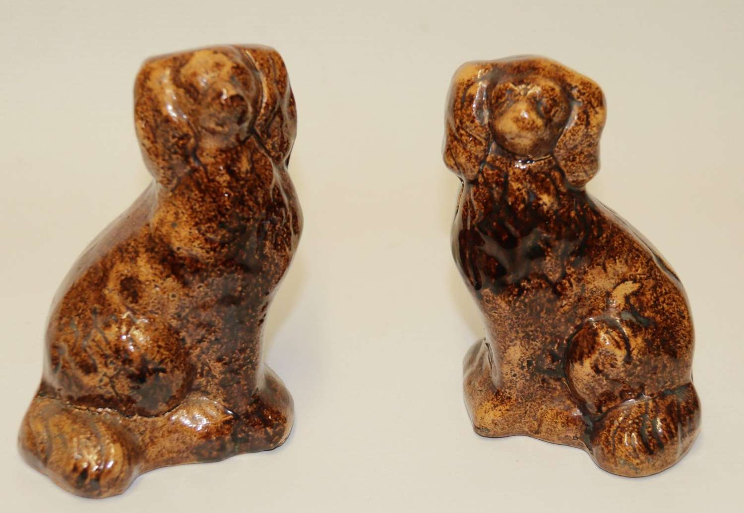 A Pair Of Early 19th Century Treacle Glazed Rockingham Pottery Spaniel Dogs